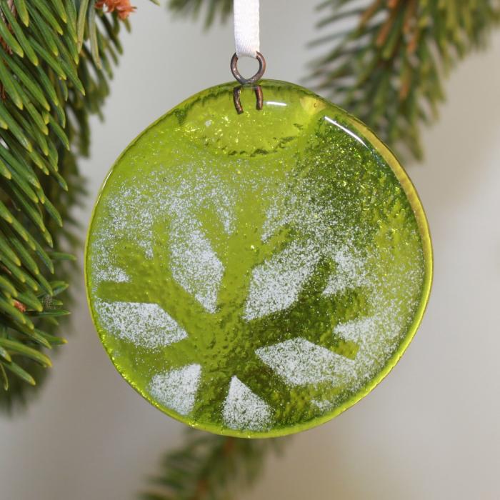 Tondo verde chiaro con fiocco di neve in negativo